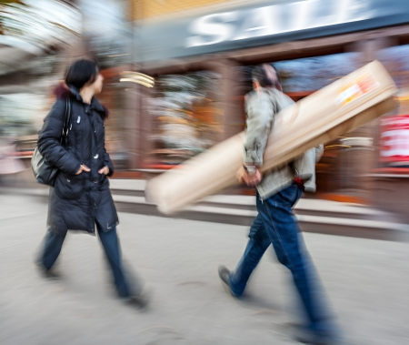 Sale. A man with a big roll and a young woman going shopping with discounts. Intentional motion blur photo