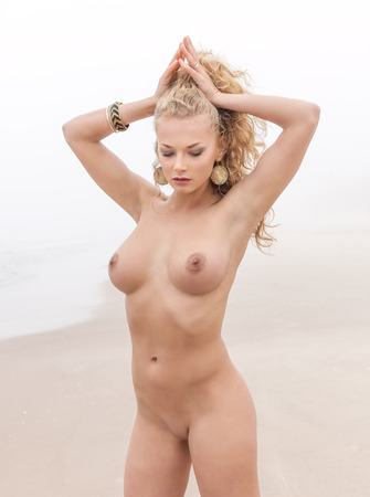 Beautiful nude woman posing on sea beach in foggy day