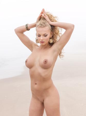 nue plage: Belle femme nue posant sur la plage de la mer dans jour de brouillard