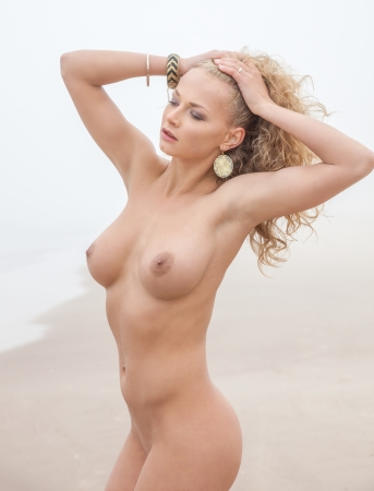 nude outdoors: Beautiful nude woman posing on sea beach in foggy day