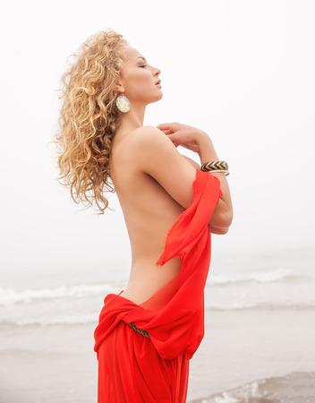 Beautiful nude woman in red fabric posing on sea beach in foggy day photo