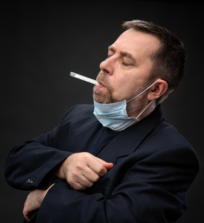prophylactic: Illness. Man in medical mask with a thermometer