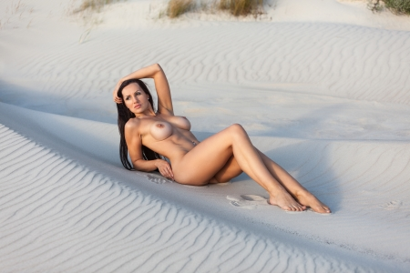 adult nude: Young nude woman on a sandy beach Stock Photo