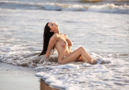 naaktstrand: Mooie jonge naakte vrouw op het strand Stockfoto