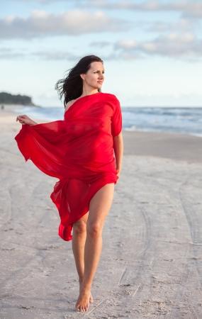 Joven mujer desnuda en una playa con tela roja photo