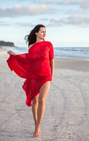 Young naked woman on a beach with red fabric photo