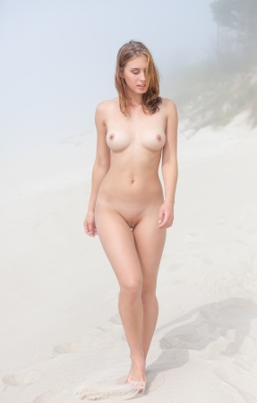 erotico: Giovane donna nuda che cammina lungo una spiaggia di sabbia in una giornata nebbiosa