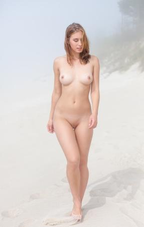 naakt: Jonge vrouw naakt wandelen langs een zandstrand op een mistige dag