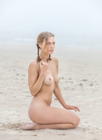 beach breast: Young nude woman on sandy beach at foggy day Stock Photo
