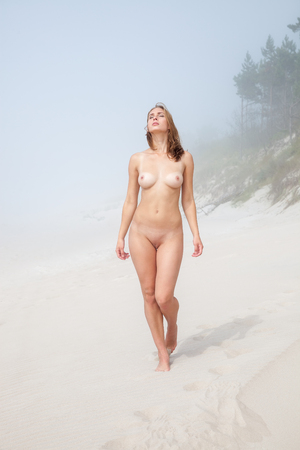 nude: Young nude woman walking along a sandy beach on a foggy day Stock Photo
