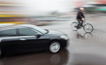 road bike: Dangerous city traffic situation with a cyclist and cars in motion blur