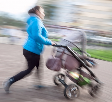 Mother with small children and a pram walking down the street. Intentional motion blur photo