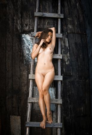 cuerpos desnudos: Joven mujer desnuda de pie en una escalera de madera