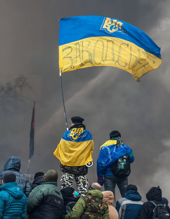 barricades: KIEV, UKRAINE - January 25, 2014: Mass anti-government protests in Kiev. People stand with national flags on barricades against a wall of smoke and water jets  on Hrushevskoho St.   Editorial