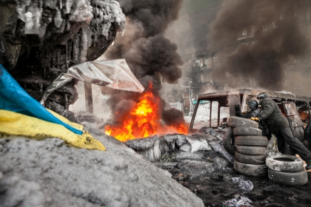 insurrection: KIEV, UKRAINE - January 25, 2014: Mass anti-government protests in the center of Kiev. Protesters burn tires in the conflict zone on the Hrushevskoho St.  Editorial