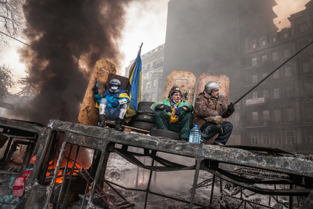 barricades: KIEV, UKRAINE - January 25, 2014: Mass anti-government protests in the center of Kiev. Protesters rest on the barricades on the Hrushevskoho St.