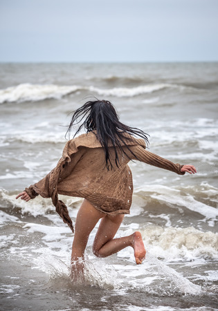 sexy naked girl: Beautiful young seminude woman in the cold sea waves