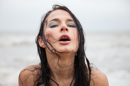 Portrait if frozen wet young woman on cold sea background photo
