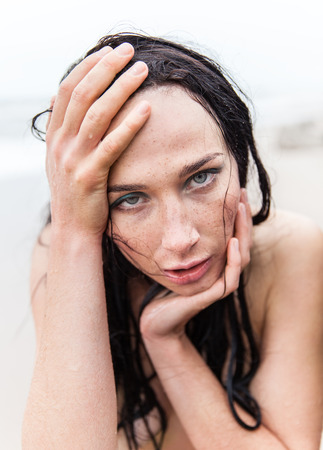 Portrait of frozen wet seminude young woman on cold sea background photo