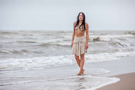 Beautiful young seminude woman in the cold sea waves photo