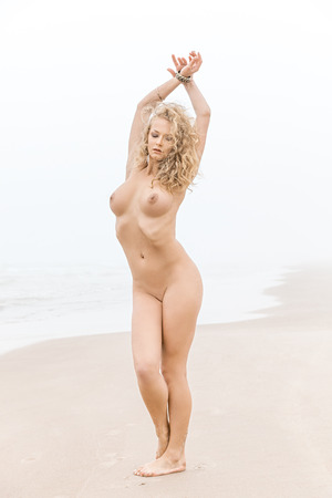 Beautiful nude woman posing on sea beach in foggy day