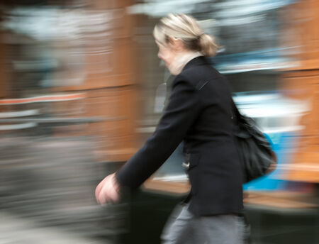 Woman  walking in the street. Intentional motion blur photo