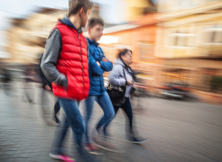 Abstract image of a young people group hurrying about their business. Intentional motion blur photo