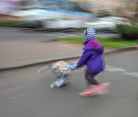 Little girl with toy stroller crossing the road.  Intentional motion blur photo