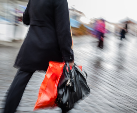 Abstract image of a woman walking down the street in the rain with a red package and black bag.  photo