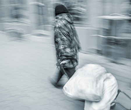 An elderly woman carries bags down the street on a trolley.  Intentional motion blur photo