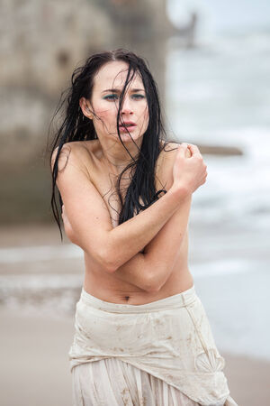 Frozen wet seminude young woman on cold sea  photo
