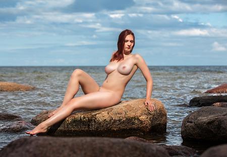 mujer desnuda sentada: Joven mujer desnuda sentada sobre la piedra contra el fondo del mar