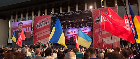 electorate: UZHGOROD, UKRAINE - MAY 1, 2014: Most rating Ukrainian presidential candidate Petro Poroshenko speaks at election meeting in Uzhgorod. On the poster: Live in new ways. Petro Poroshenko Editorial