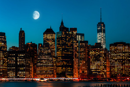 Manhattan at night with moon, lights and reflections. New York City skyline