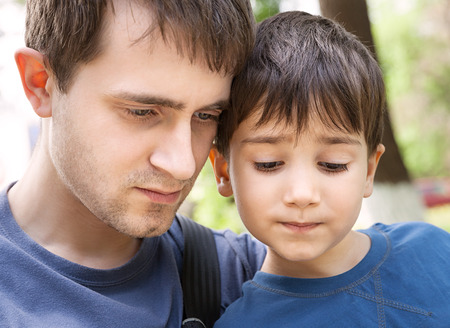 Father and son with interest looking at something togethe. Focus on boy