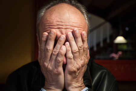 Depression. Elderly man sitting in the cafe. Covers his face by hand
