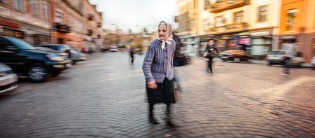 slowly: UZHGOROD, Ucrania - 25 de octubre 2013: La mujer mayor sola en un chal y un suéter de lana de pie en una plaza pavimentada de la ciudad en la madrugada. El desenfoque de movimiento intencional