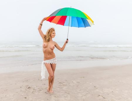 young nude girl: Junge nackte M�dchen mit einem bunten Sonnenschirm am Strand