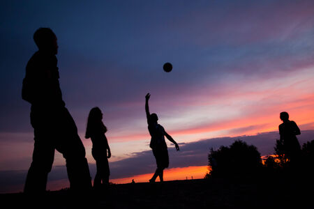 Night scene. Silhouettes of young people playing with a ball on the sunset sky background photo