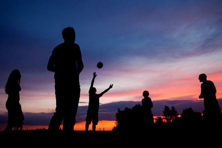 Night scene. Silhouettes of young people playing with a ball\ on the sunset sky background