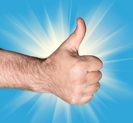 gratified: Body part. Thumb up sign on a blue background with sunlight rays Stock Photo