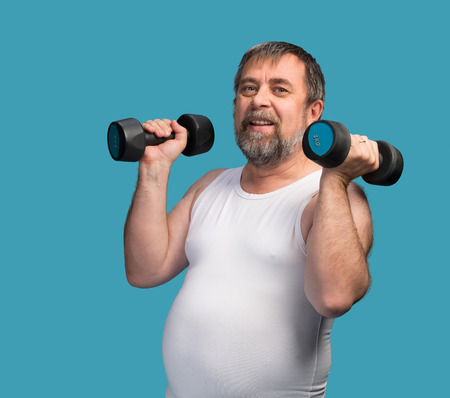 paunch: Middle-aged man with a paunch exercising with dumbbells on blue background