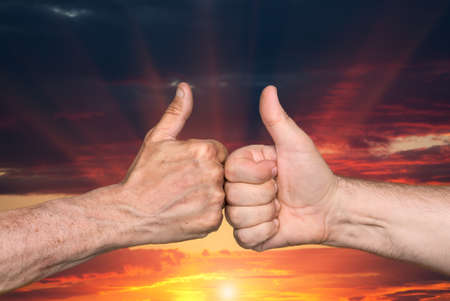 gratified: Partnership. Thumbs up sign on sunset sky background