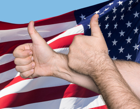 gratified: Patriotic concept. Thumbs up sign against of United States of America flag