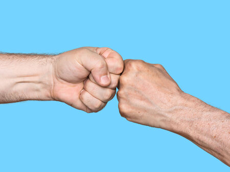 bump: Two men bumping fists isolated on blue background