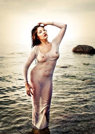 wet nude: Una mujer desnuda h�meda con una camisa transparente contra el mar.