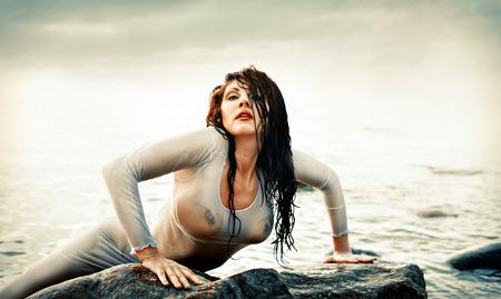 wet nude: Una mujer desnuda h�meda con una camisa transparente en el fondo del mar