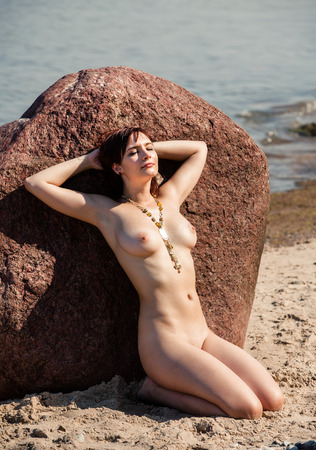 Young naked woman sunbathing near the stone on sea background photo