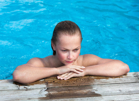 Beautiful young naked woman in swimming pool photo