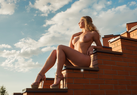 Young beautiful naked woman posing on the stairs in the evening sun photo